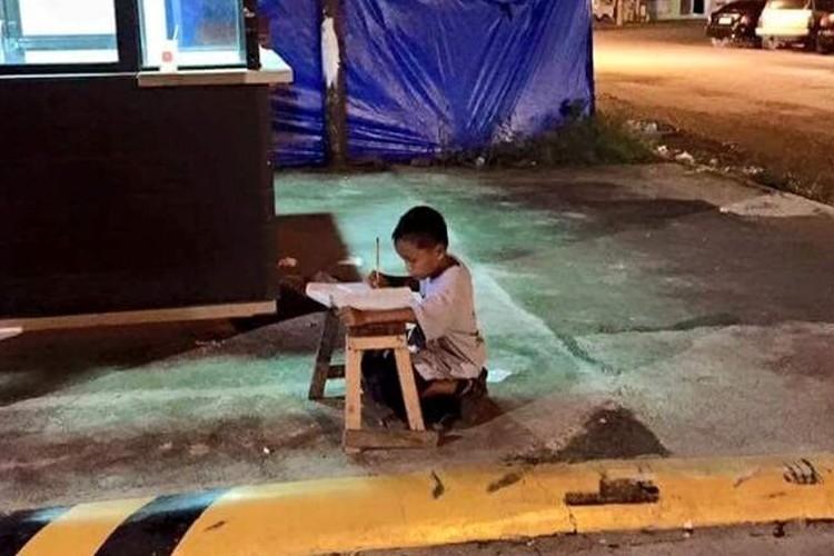 """""""歩道で勉強する少年""""の画像に、世界中の人々の心が動かされている!"""