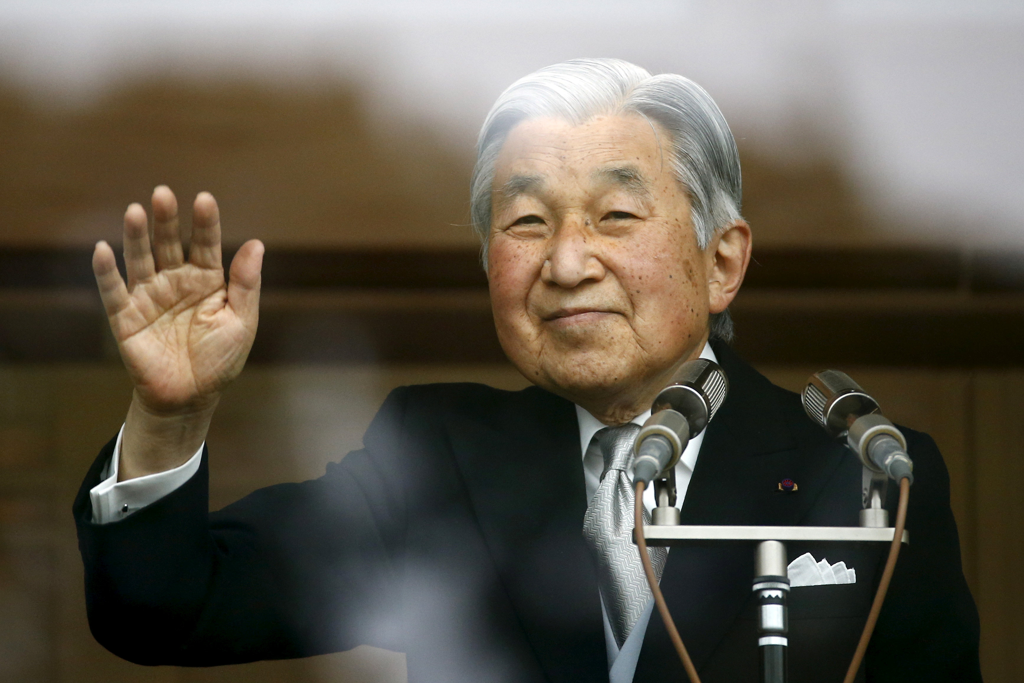 Japan's Emperor Akihito's waves to well-wishers at the Imperial Palace in Tokyo