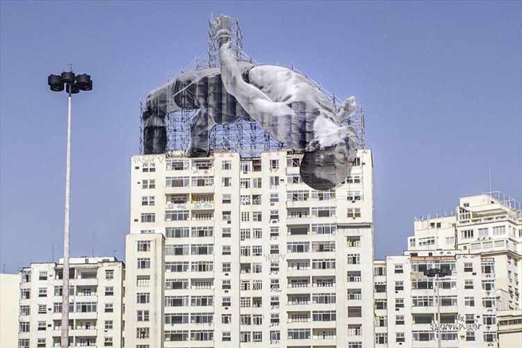 高跳びの選手がビルを越える! 五輪で盛り上がるリオの街に巨大アートが登場!