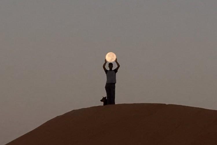 『お月さん、捕まえた!』まるで月と戯れているかのような写真が面白い