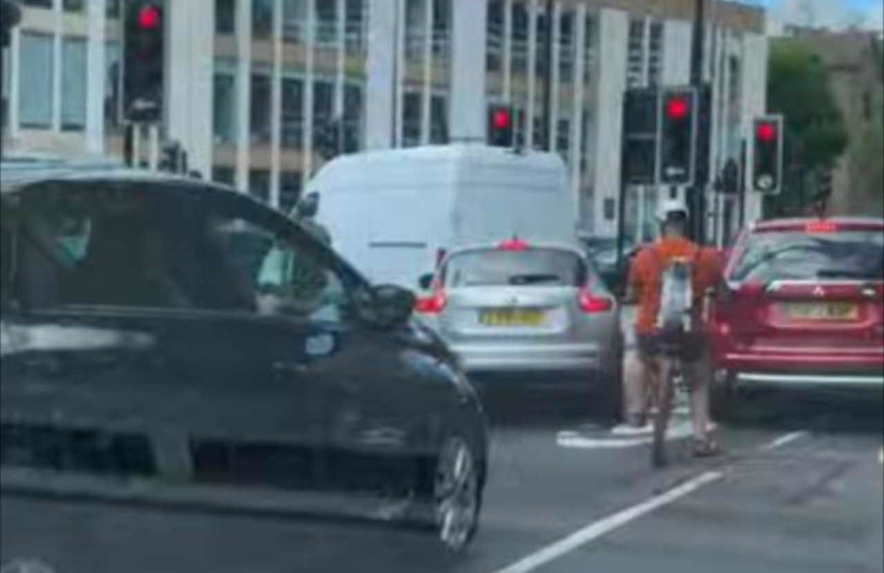 前を行く自転車に乗るライダーに背負われているイヌ。よく見るとその姿がワイルド&クールだった!!
